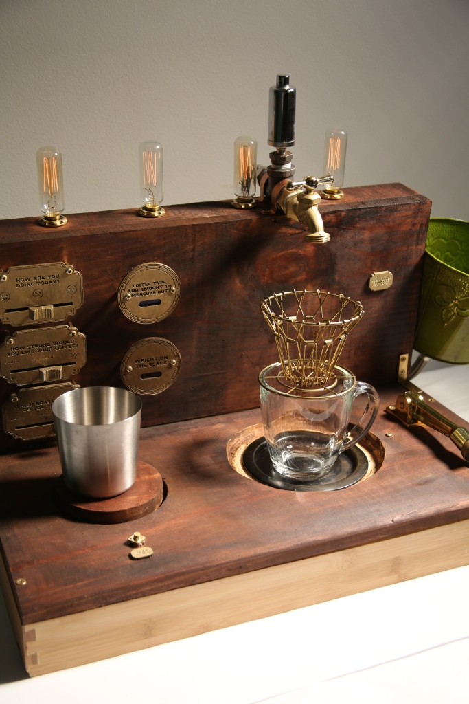 An image of a Steampunk style Coffee Machine. Made from light pine wood that was stained in dark brown color. Most materials are vintage, or made to look vintage. Inspired by the Roaring 20s, retro-futuristic art style and a lot of brass and gold. The machine is about 24 inches long and 12 inches deep. It looks like a half-way opened suitcase. There are 4 incandescent light bulbs at the top that are dimly lit. A green bucket on the left edge of the machine intended for intake of water. A hot plate on the right side of the base of the machine to heat up water.